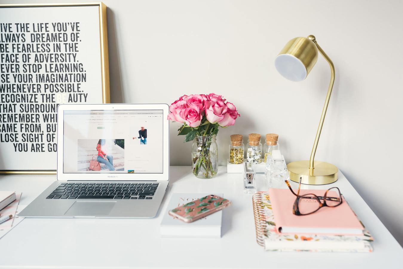 Mesa com frase motivacional, uma luminária e um notebook