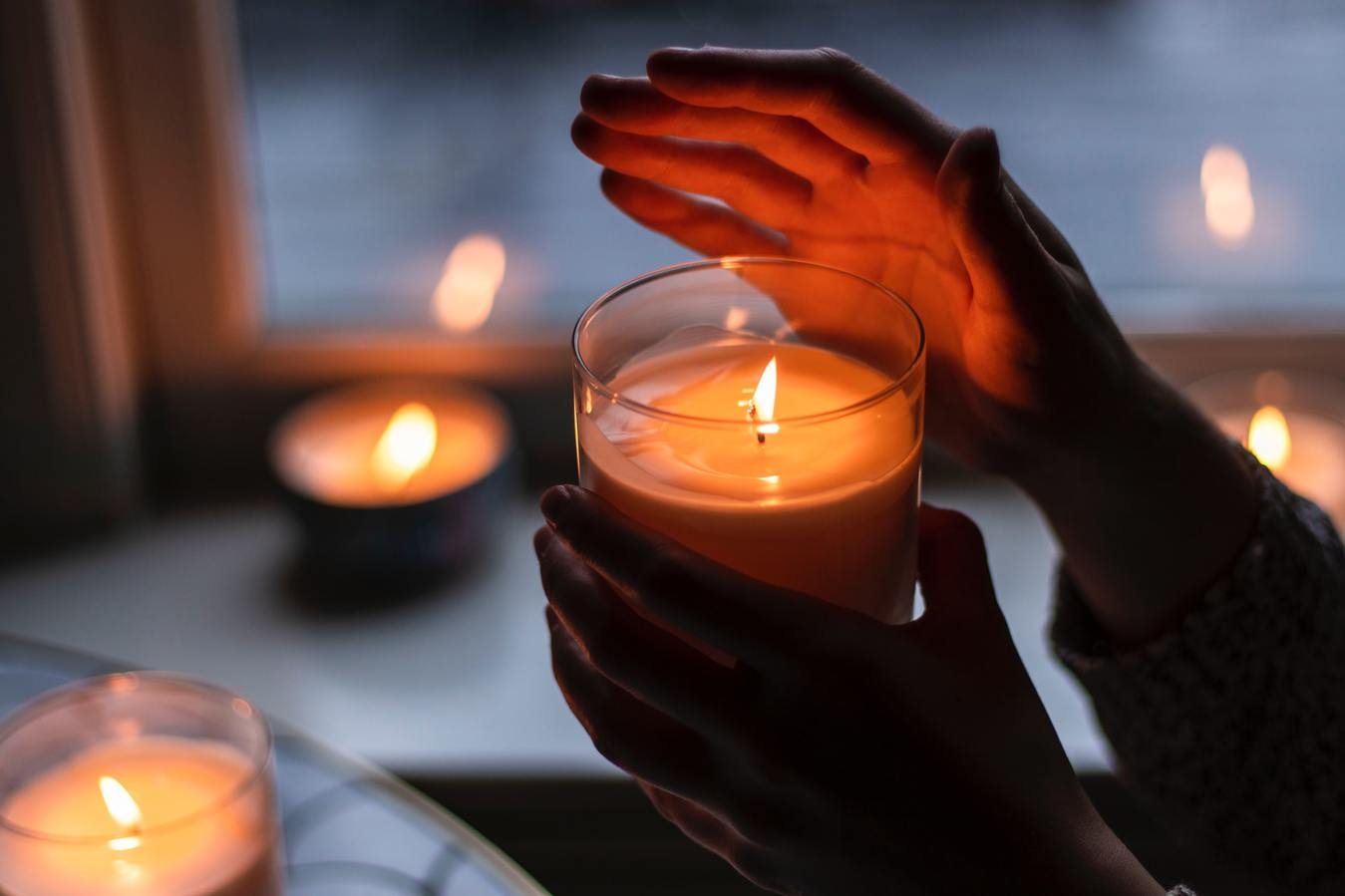 Hand Shielding a Candle in the Dark