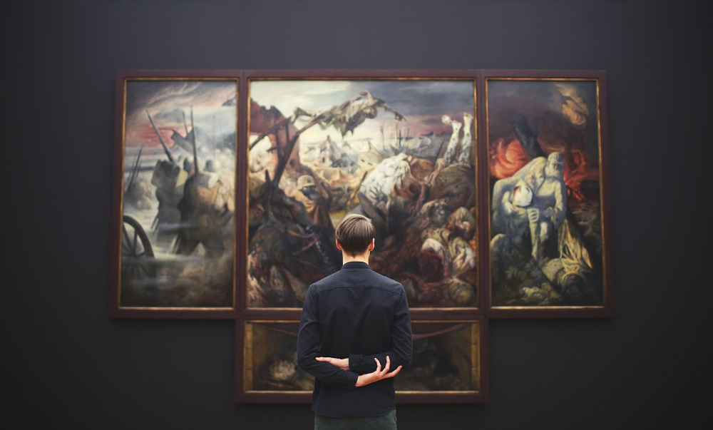 homem a olhar para uma obra de arte grande na parede da galeria