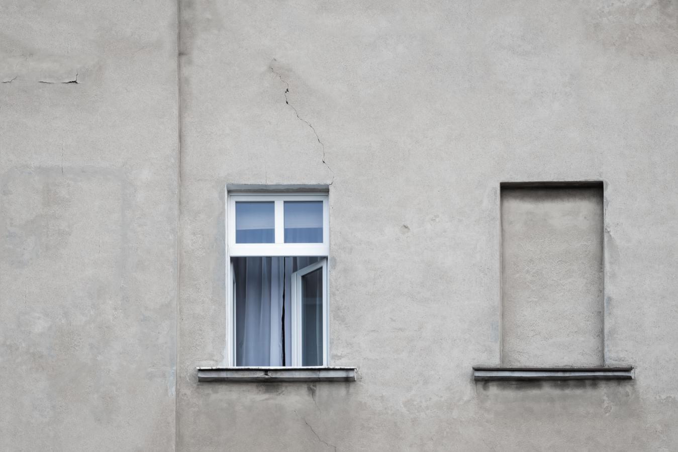 Uma janela aberta ao lado de uma janela fechada com cimento
