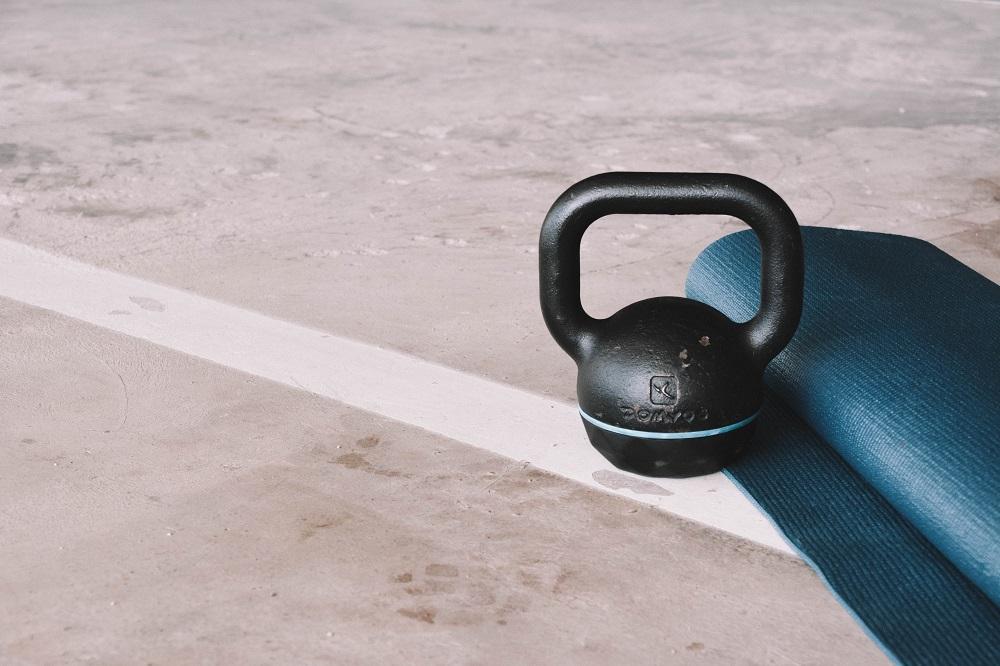 kettlebell ao lado de um tapete de ioga dobrado no chão de concreto
