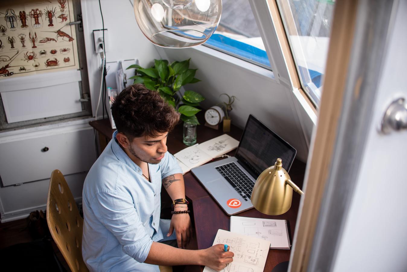 Человек, просматривающий интернет-магазин на планшете рядом с растениями