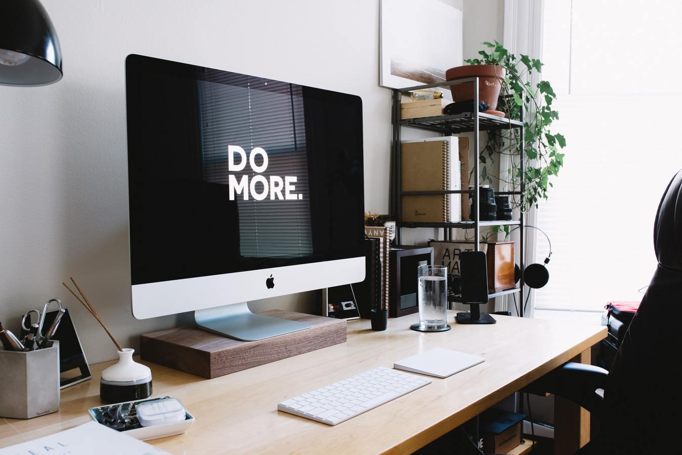 iMac di atas meja di samping rak