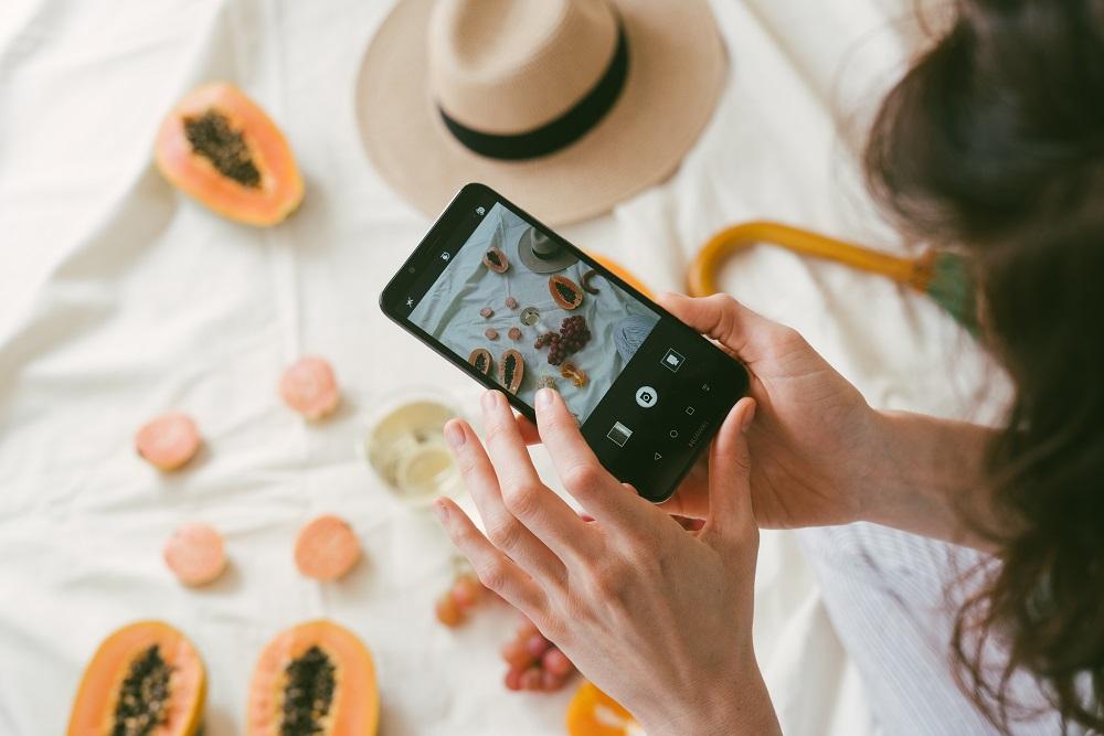mujer tomando fotos de comida en el teléfono