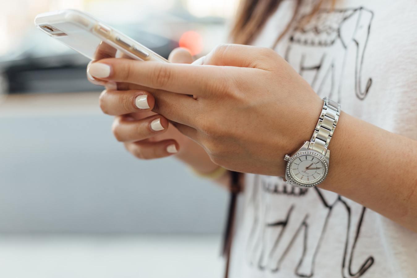 Mulher segurando celular, braço com relógio