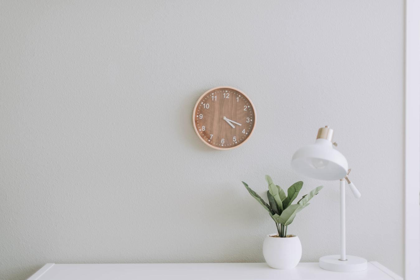 Um relógio de parede acima de uma mesa com uma planta e uma luminária