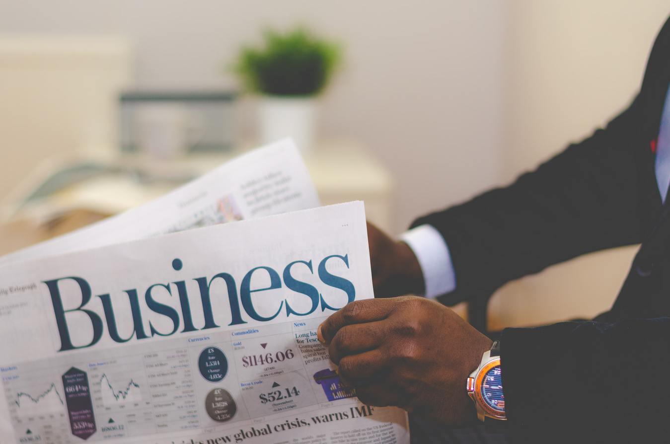 Una persona in giacca e cravatta che legge un giornale di affari