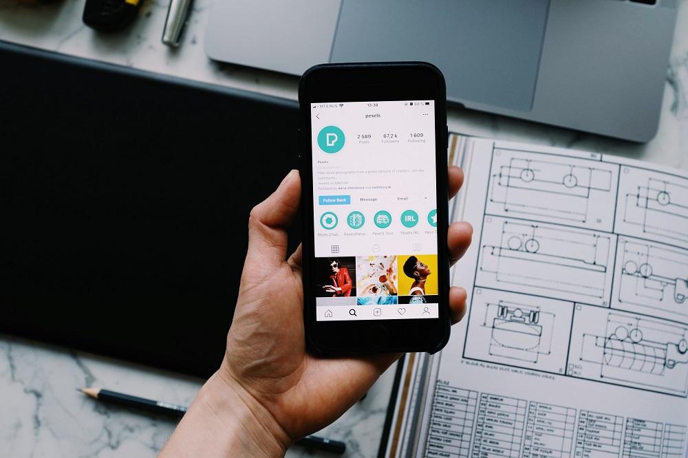 Mano sosteniendo un teléfono que muestra un perfil de negocios de Instagram