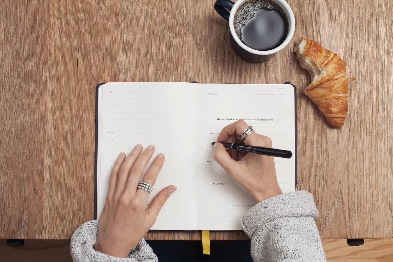 Persoon die in een dagboek schrijft met koffie en een gebakje
