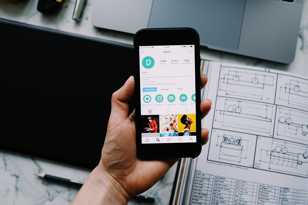 mão segurando um celular mostrando perfil de uma empresa no Instagram