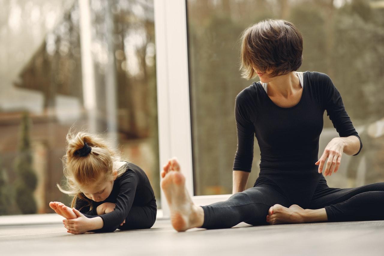 Professora de ioga ensinando criança uma posição de ioga