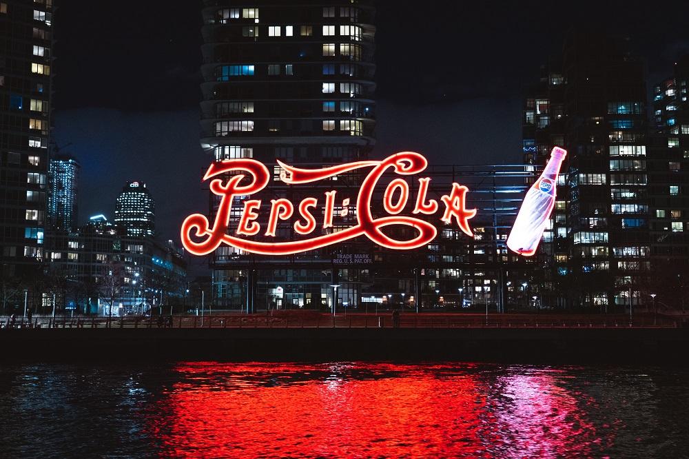 grande e luminosa placa da Pepsi em frente a prédios