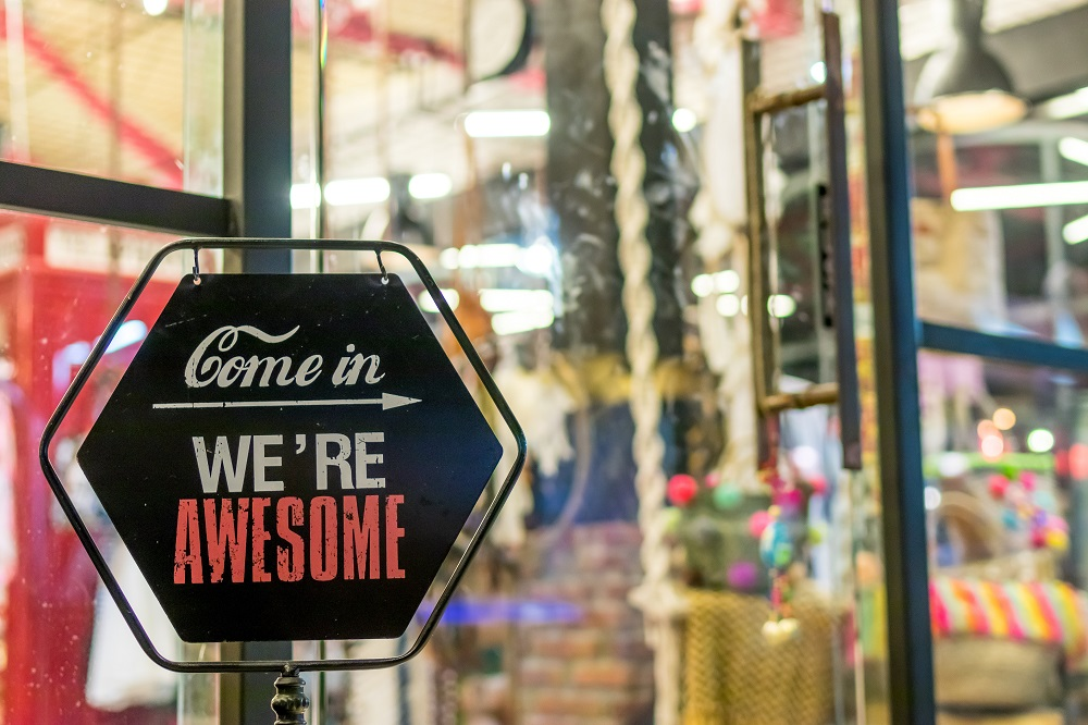 """sinal na porta dizendo """"entrem, somos fantásticos""""."""