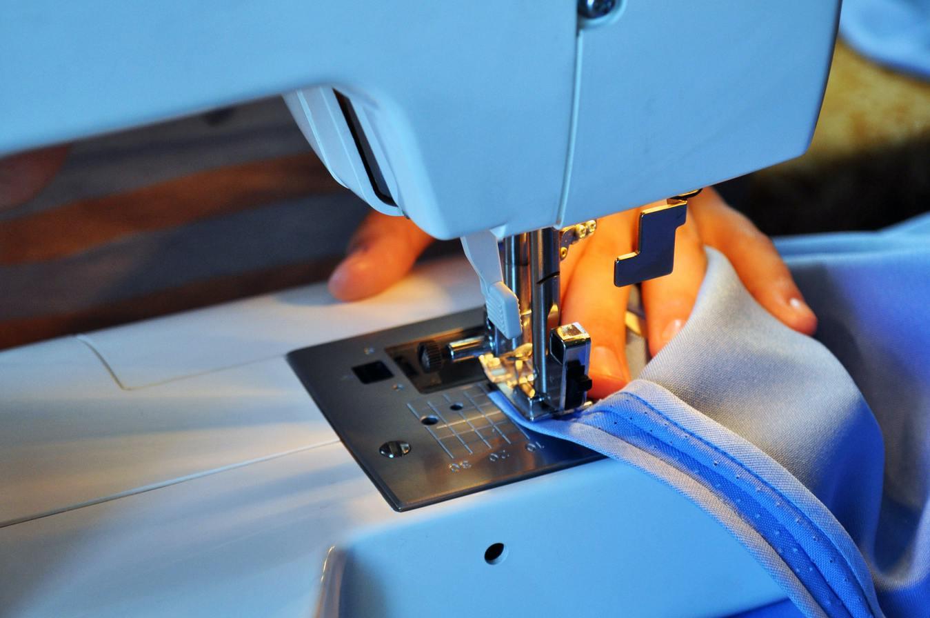 mão movendo tecido na máquina de costura