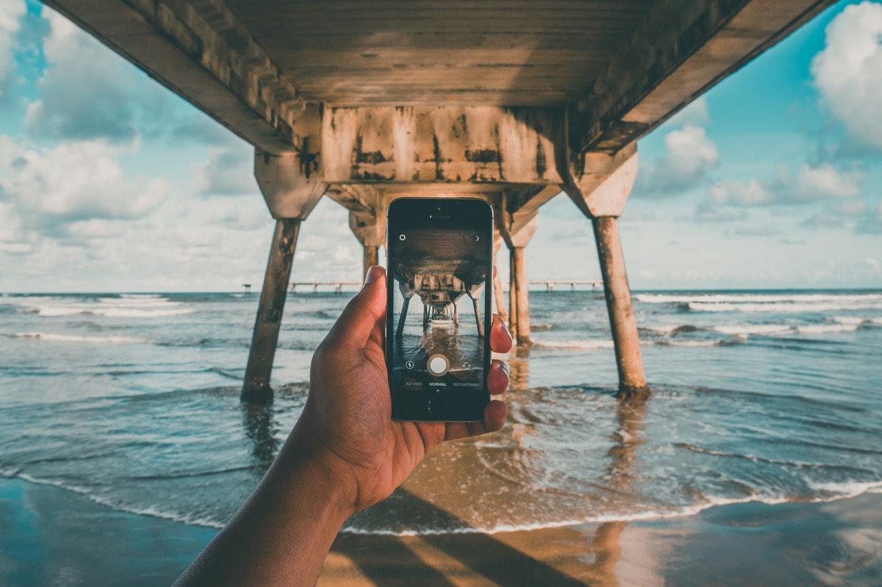Tirando foto perto da água na praia debaixo de uma ponte