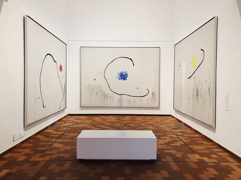 três pinturas grandes numa galeria de arte