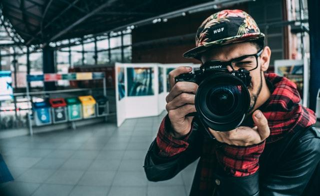 Uomo giovane che scatta foto con macchina fotografica