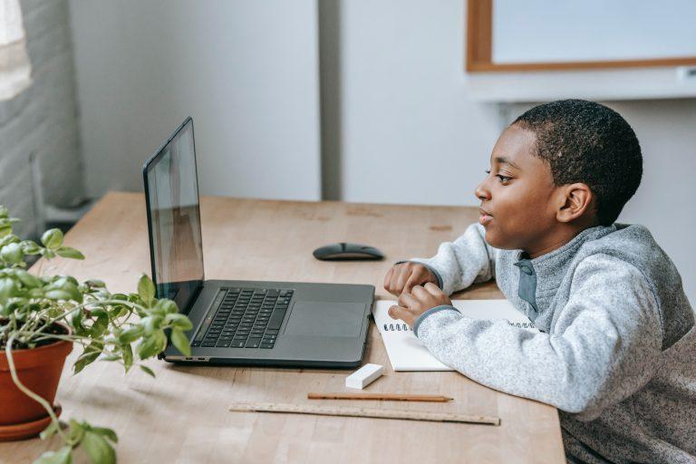 Seorang anak membuka laptop di meja