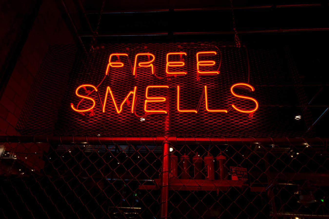 Baliho neon bertuliskan Free Smells pada malam hari
