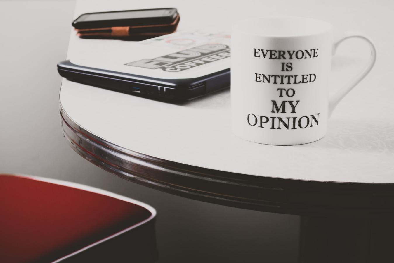 cốc ghi chữ everyone is entitled to my opinion trên bàn