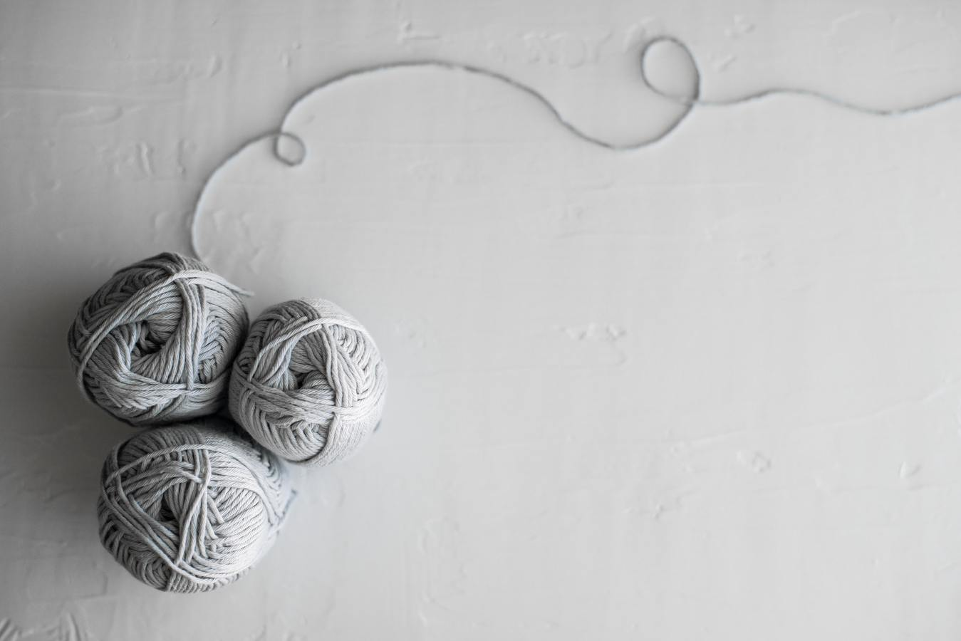 Drie ballen grijze wol
