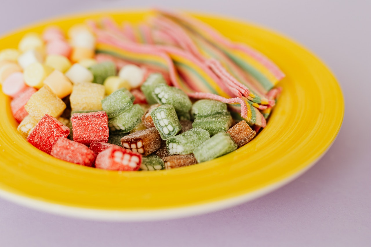 cose up de doces coloridos em um prato amarelo