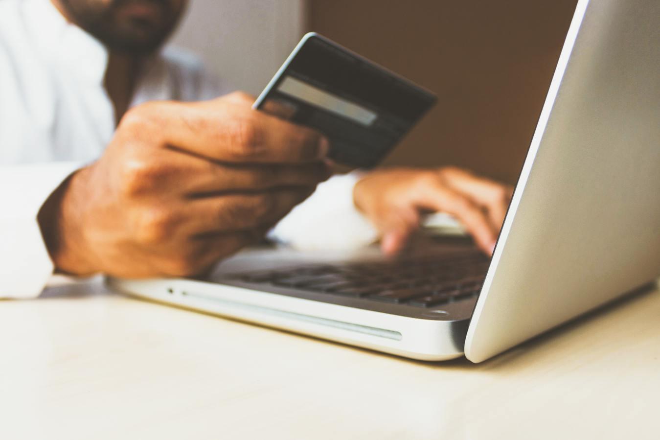 affiliate marketing là gì: người cầm thẻ đang làm việc trên máy tính
