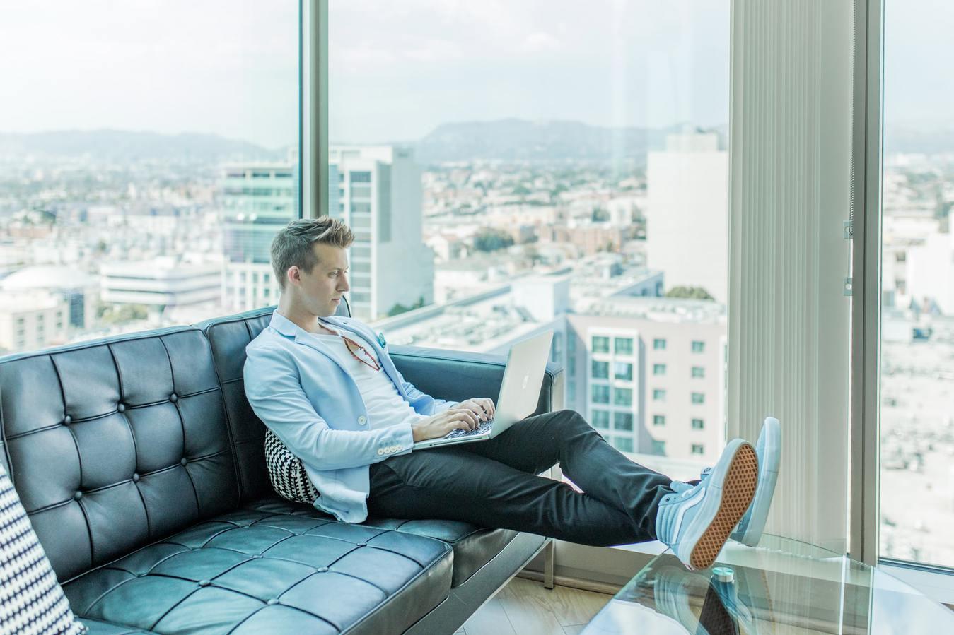 Homem sentado no sofá em um prédio alto, digitando no notebook