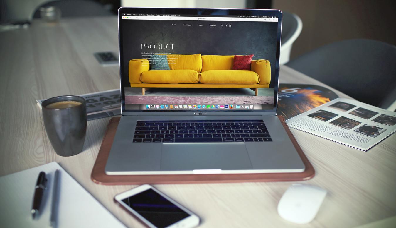 Laptop di atas meja menampilkan gambar sofa