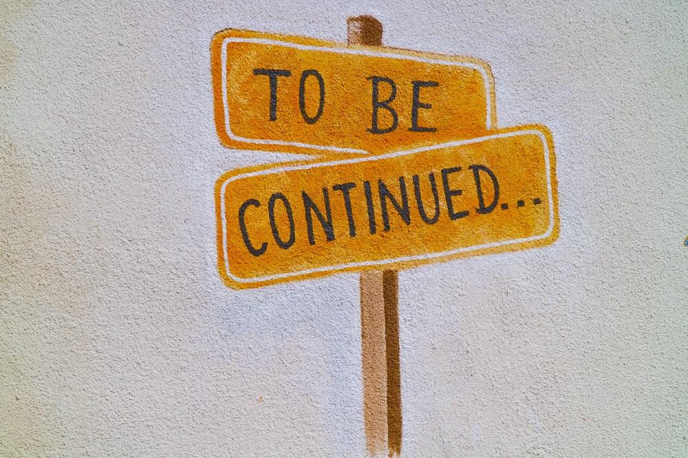 """Lukisan dinding berupa papan tanda bertuliskan """"bersambung"""""""