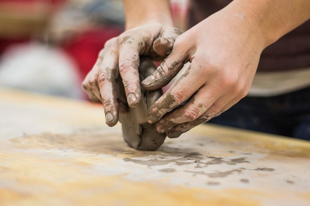 mãos esculpindo pedado de argila
