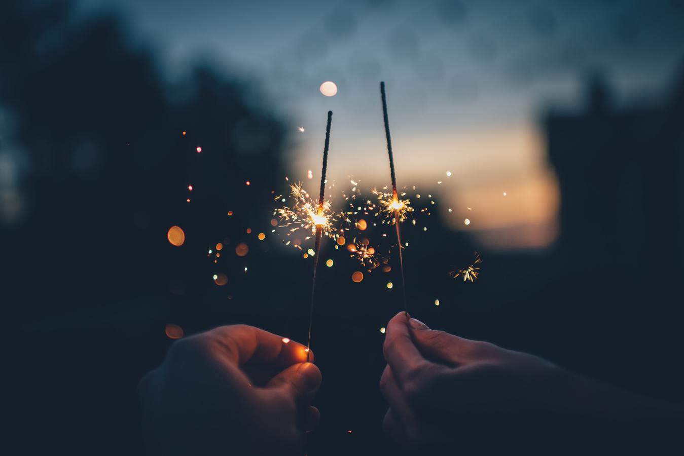 Dua orang menyalakan kembang api malam hari