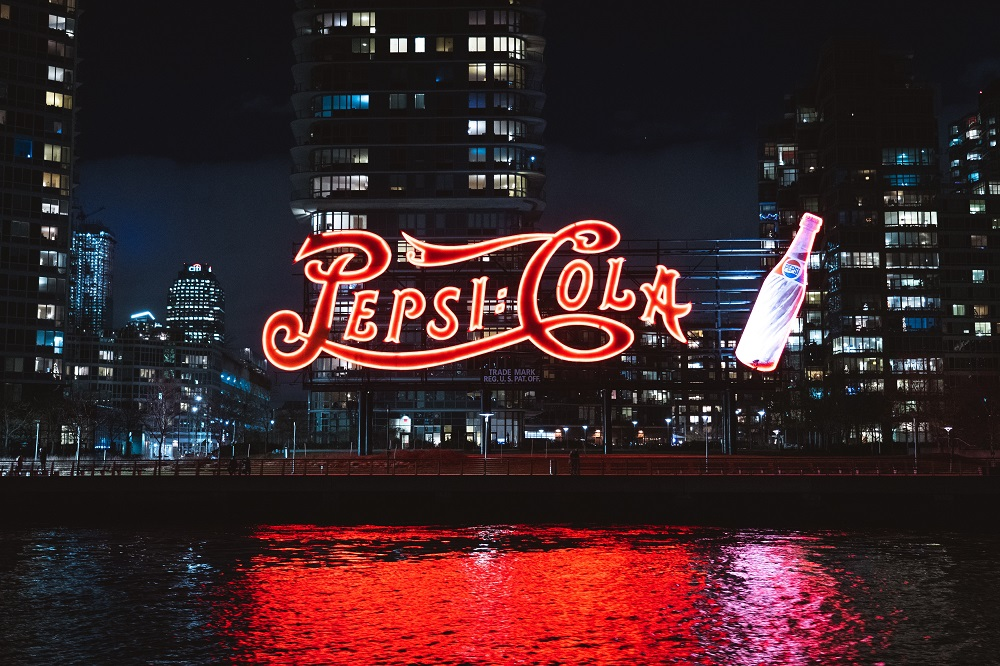 Groot verlicht pepsi cola-bord voor wolkenkrabbers