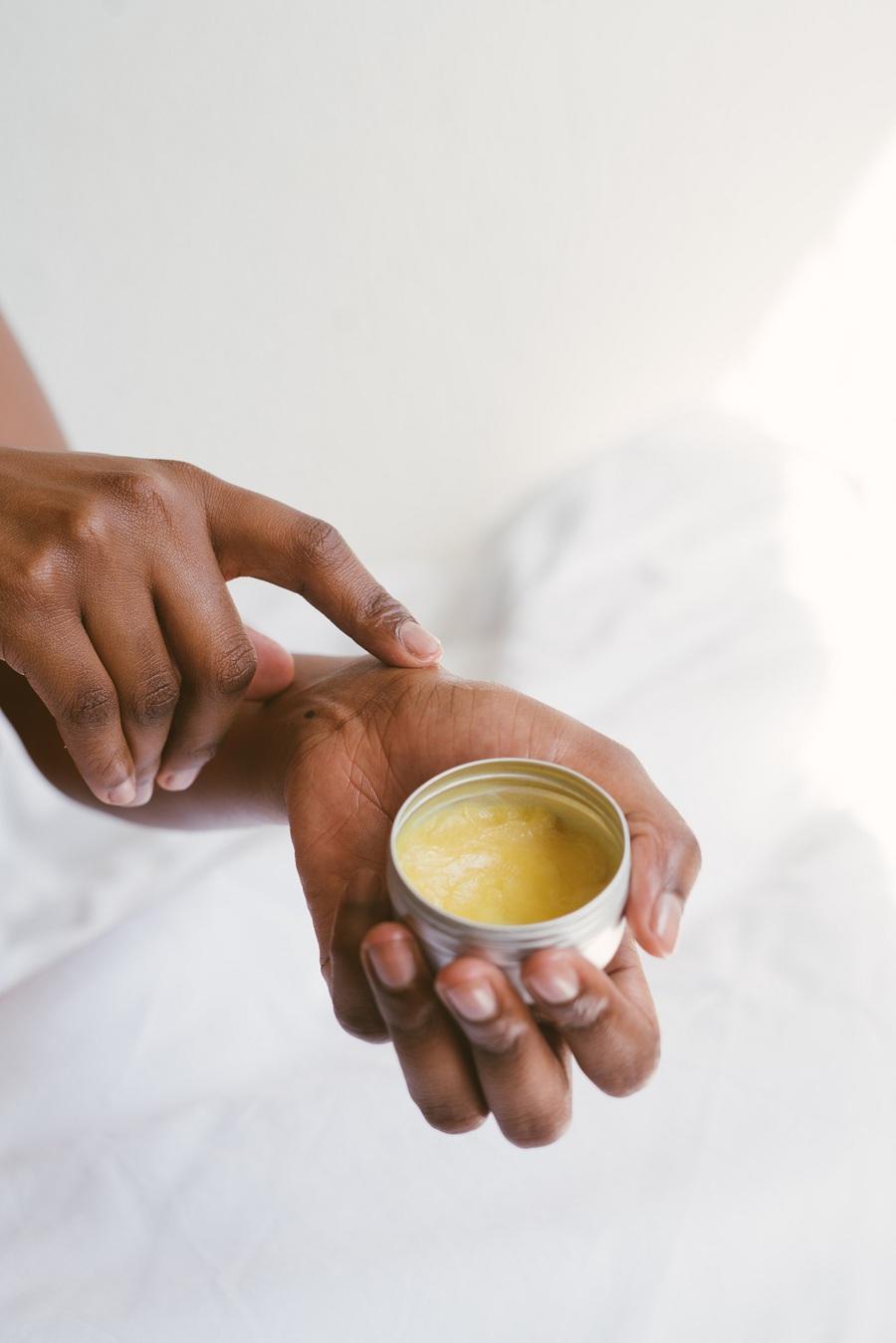 Persona con vaso di crema per le mani