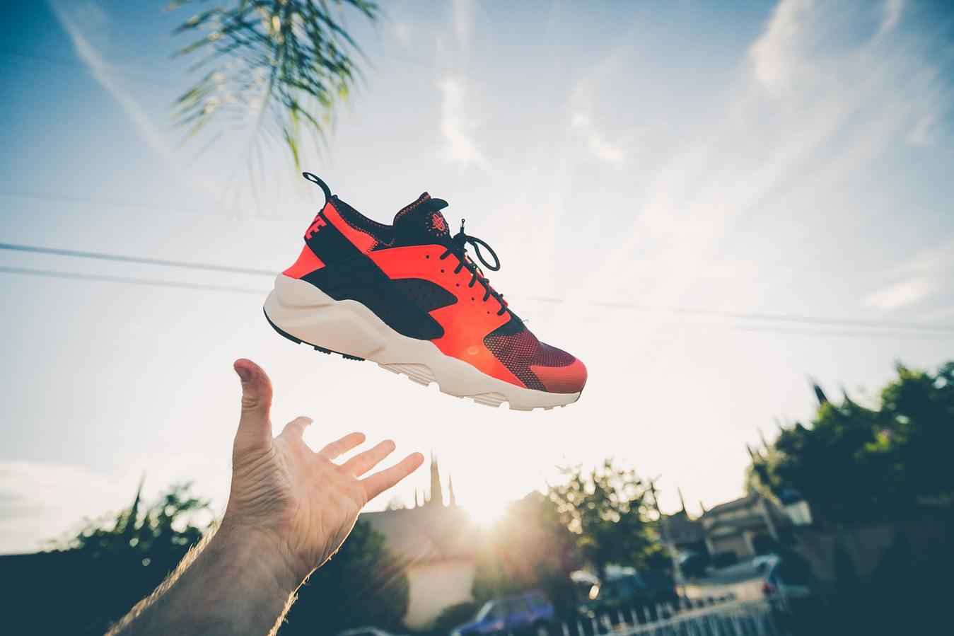 Rode sneaker in lucht gegooid