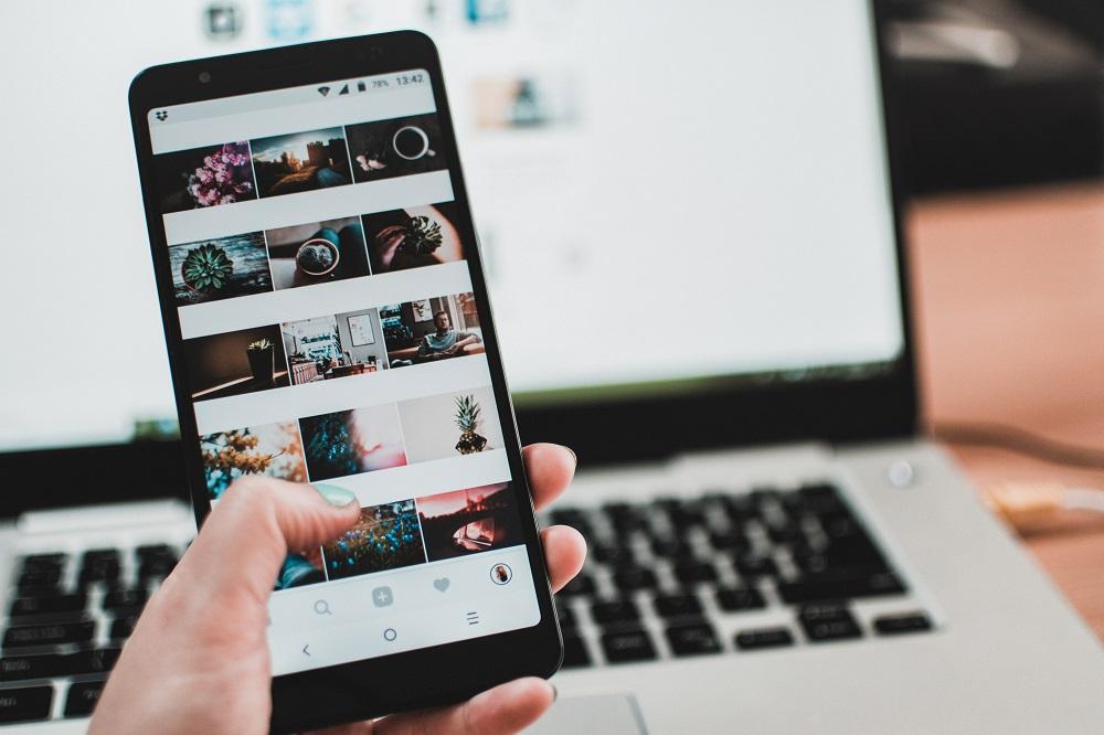 Seseorang menggulir feed Instagram di ponsel