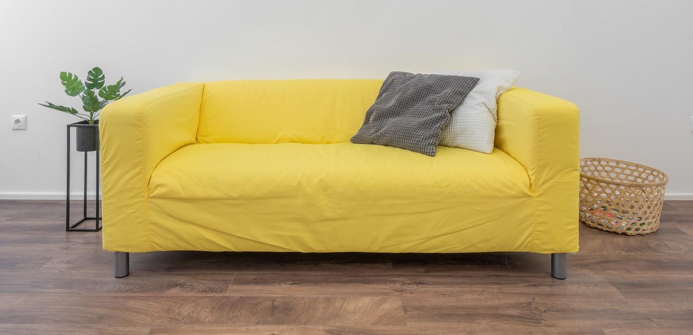 Sofa kuning dengan sarung sofa longgar
