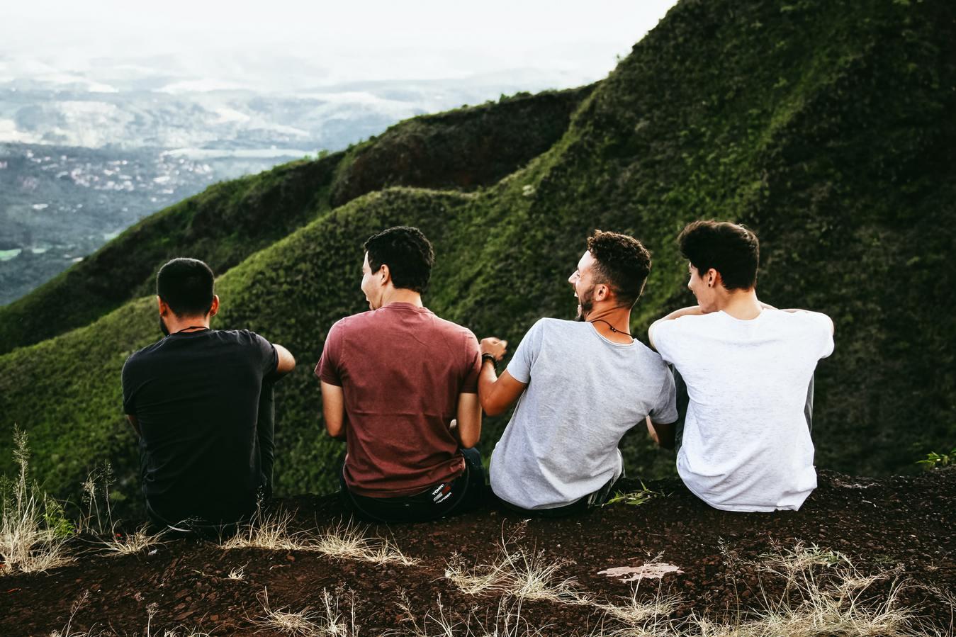 Vier mannen zittend op de berg en je ziet hun ruggen