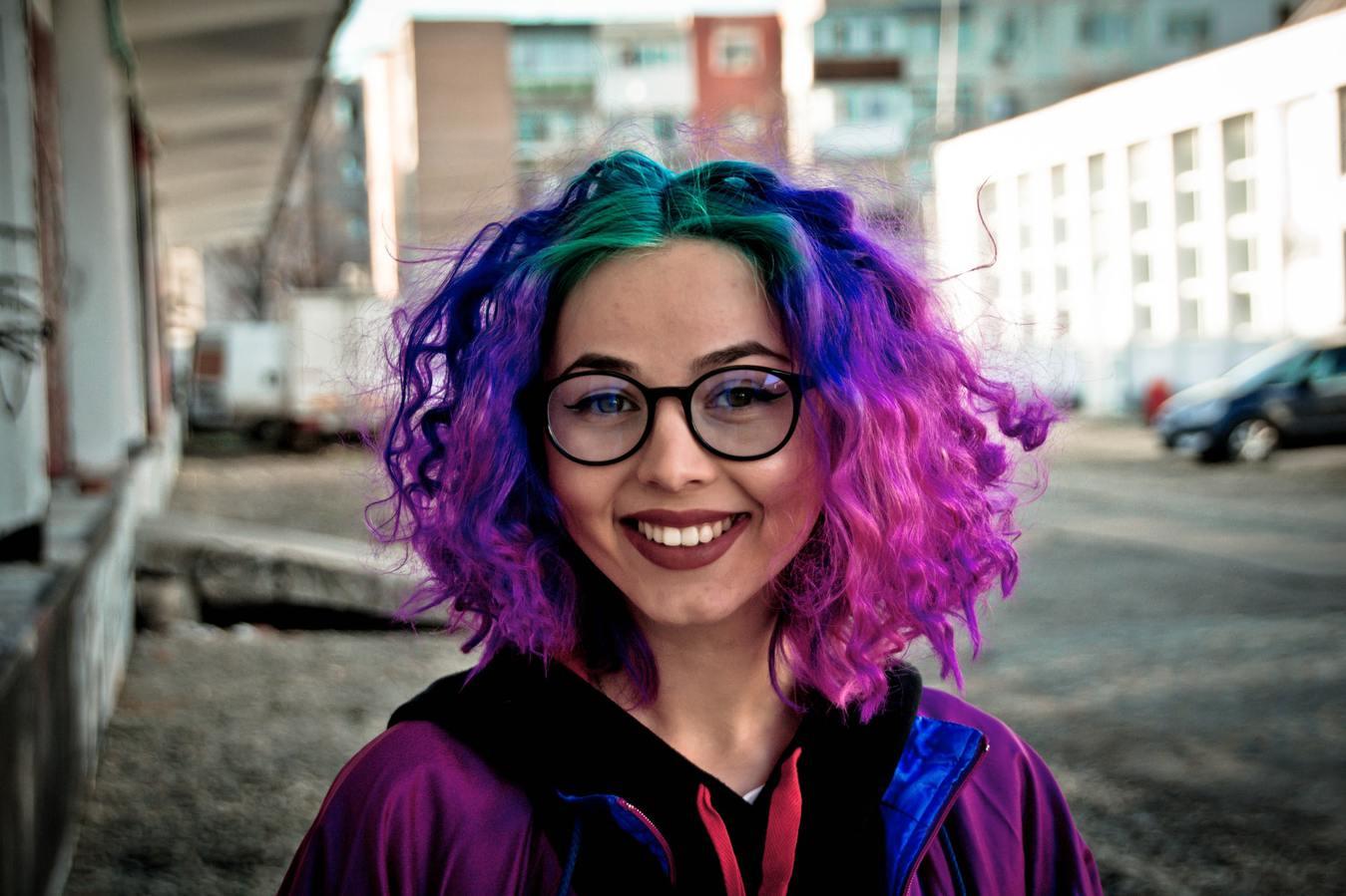 Vrouw met een kleurrijke pruik, groen, blauw en paars