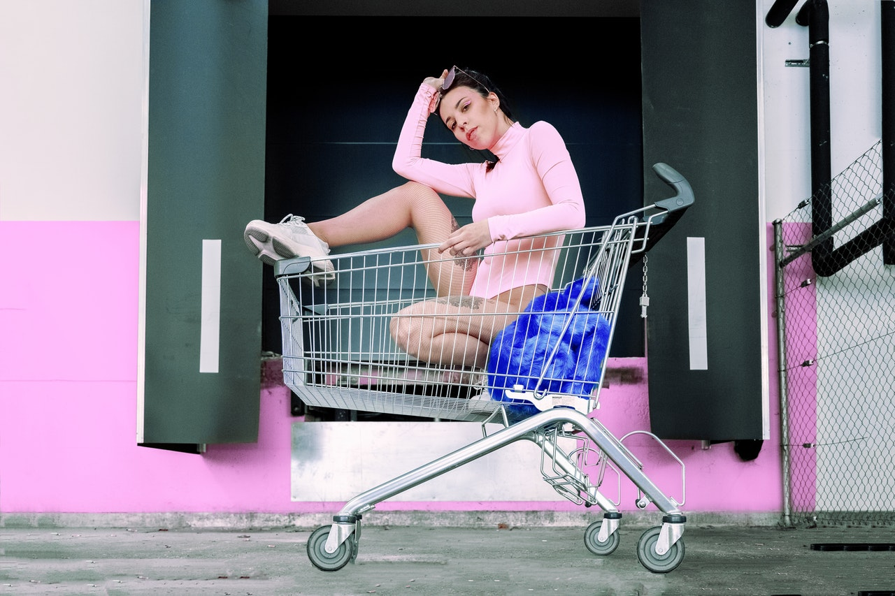 Wanita mengenakan bodysuit pink berpose di dalam troli belanja