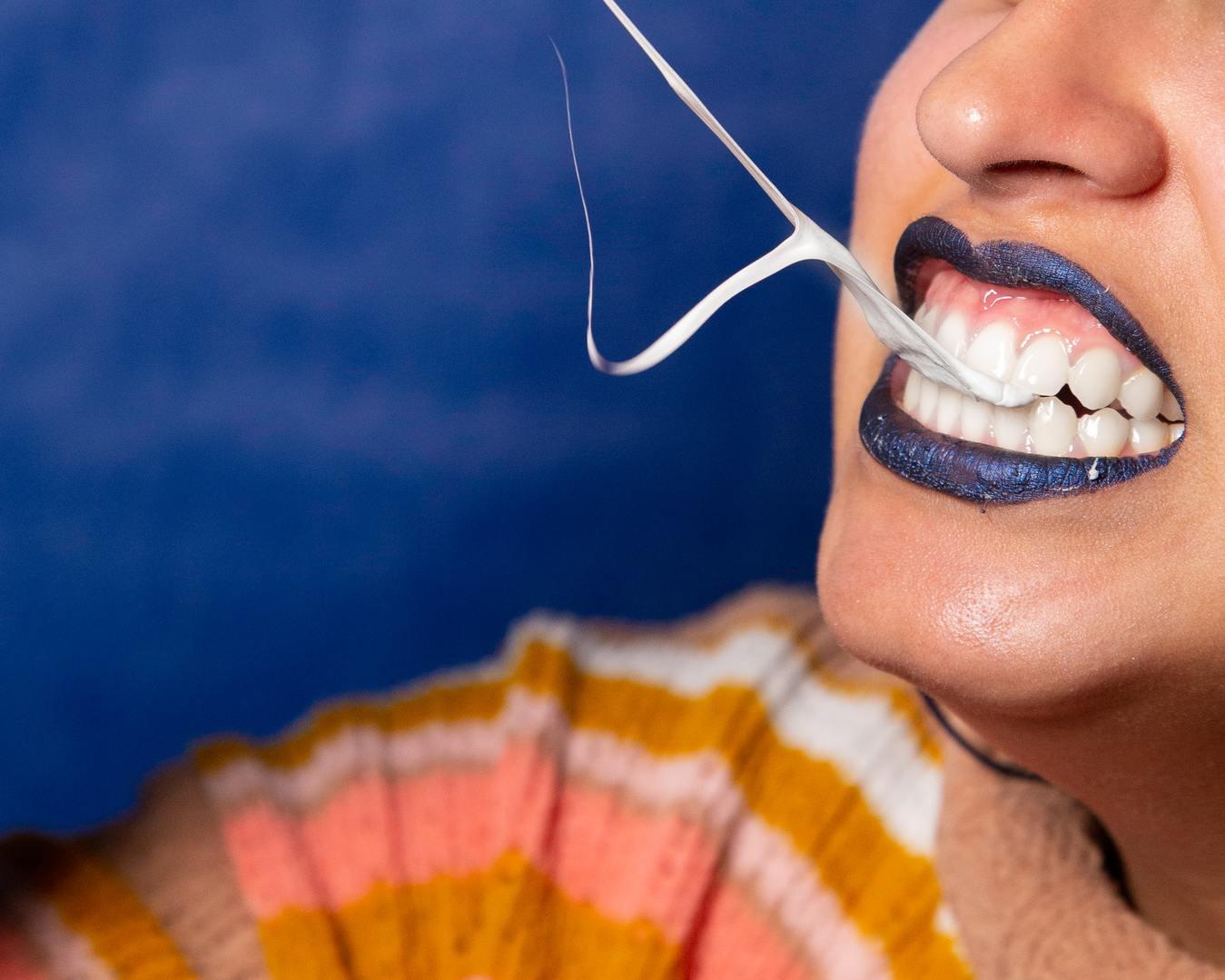 Wanita berlipstik biru mengunyah permen karet