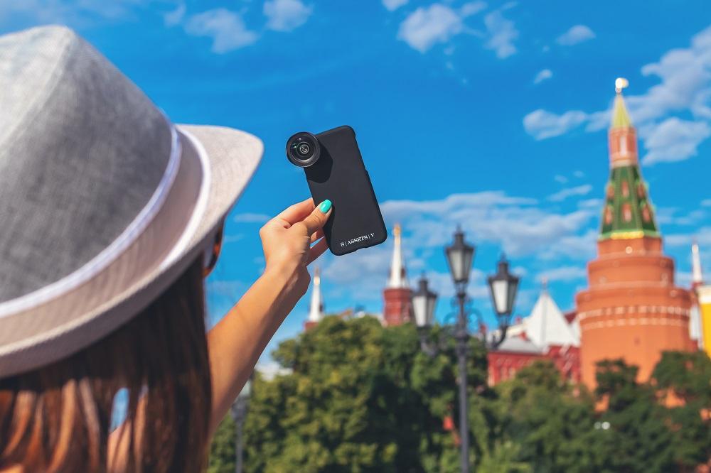 Wanita mengambil selfie dengan lensa tambahan untuk kamera ponsel