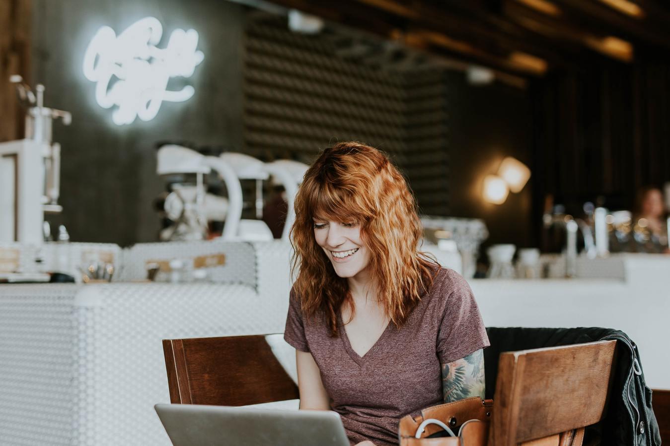 Wanita tersenyum melihat laptop di kafe