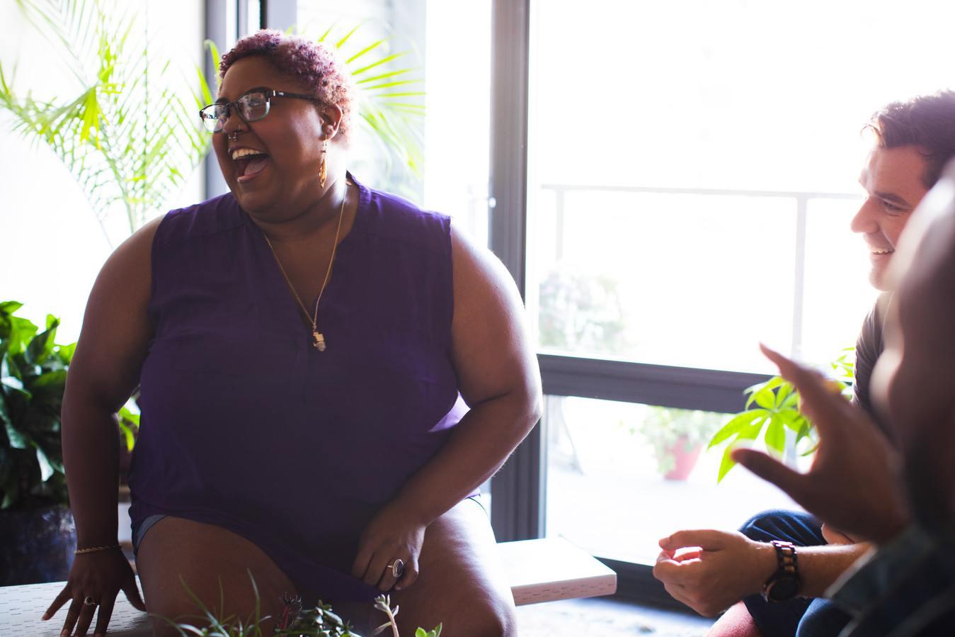 Wanita tertawa mengenakan shapewear plus size