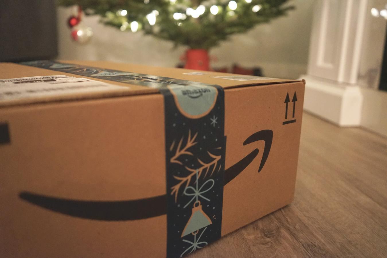 caixa de uma encomenda da Amazon com uma árvore de Natal no fundo