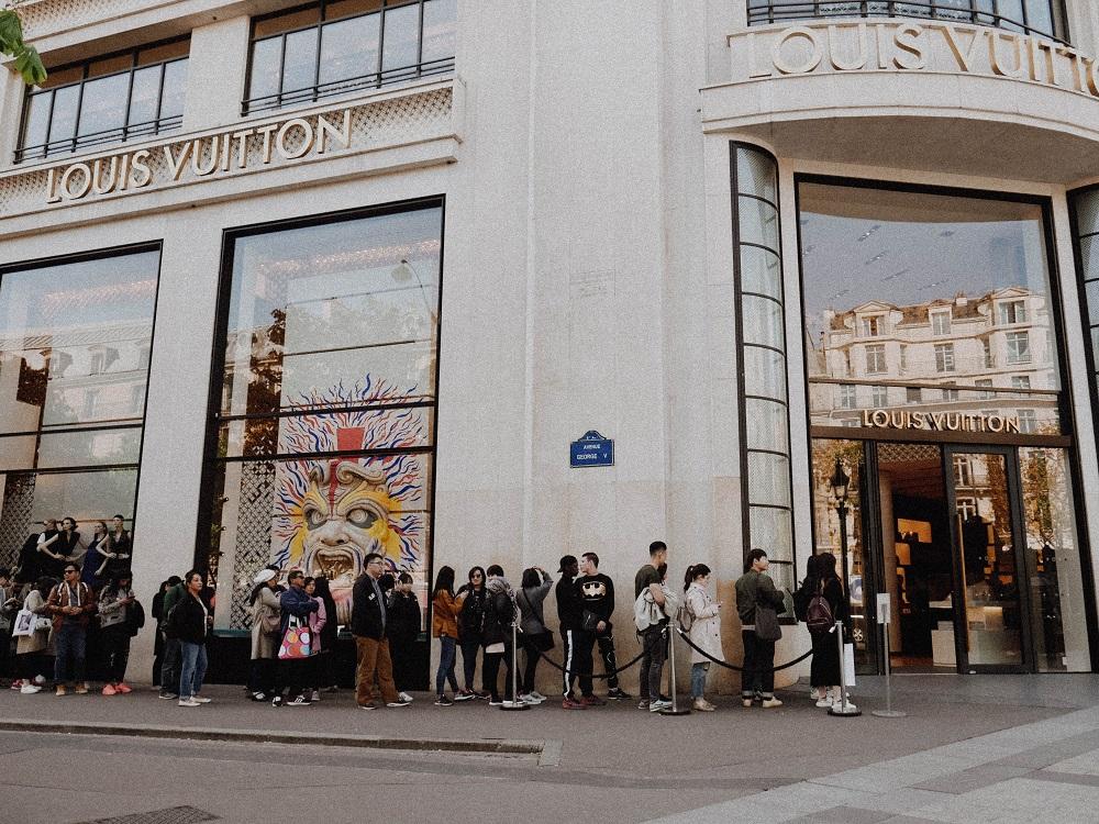 Fila de clientes à entrada de uma loja Louis Vuitton