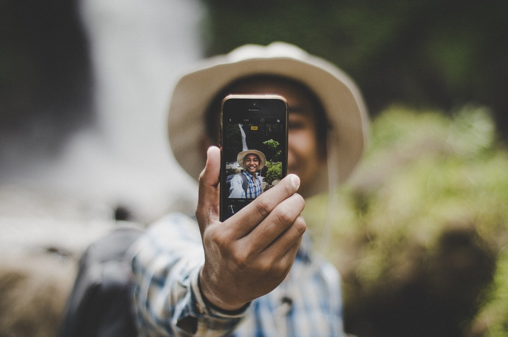 Homem com um chapéu a tirar uma selfie