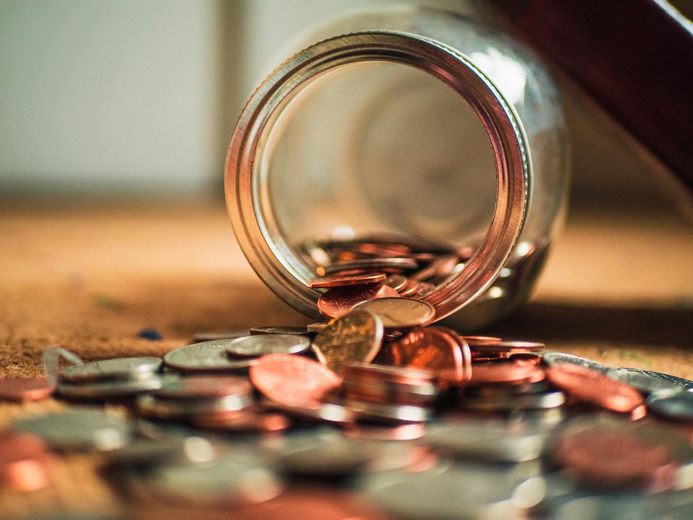 Ein Glas, das Münzen verschüttet