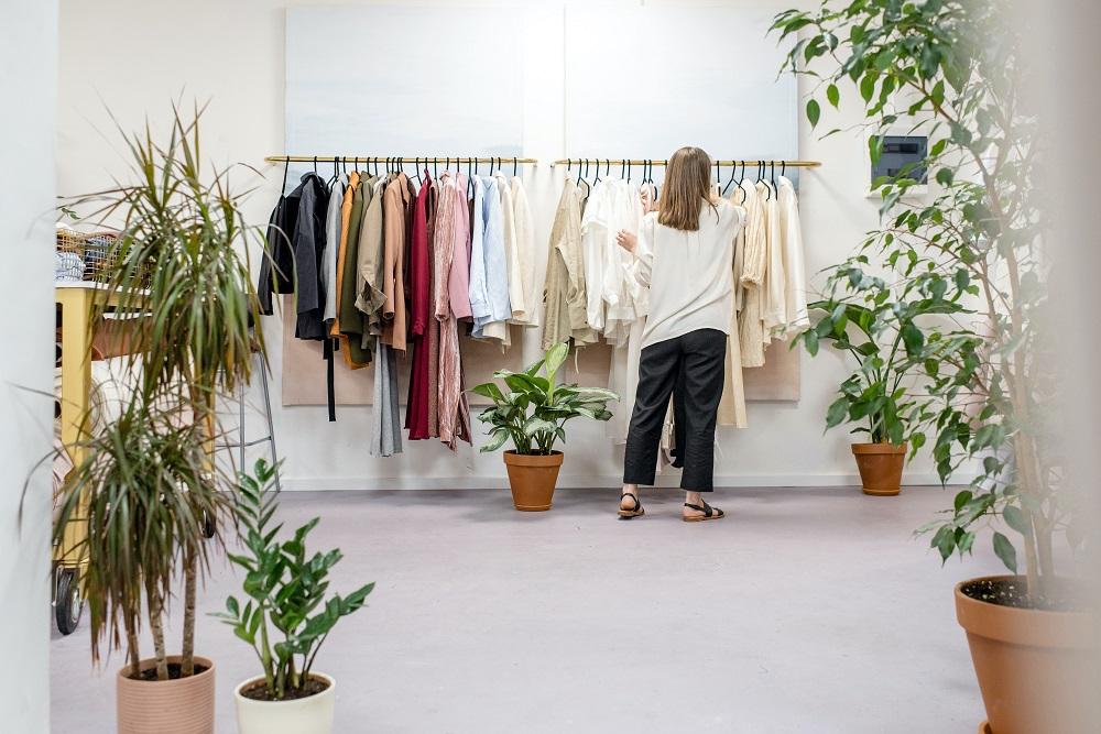 mulher a olhar para roupas em exposição em cabides