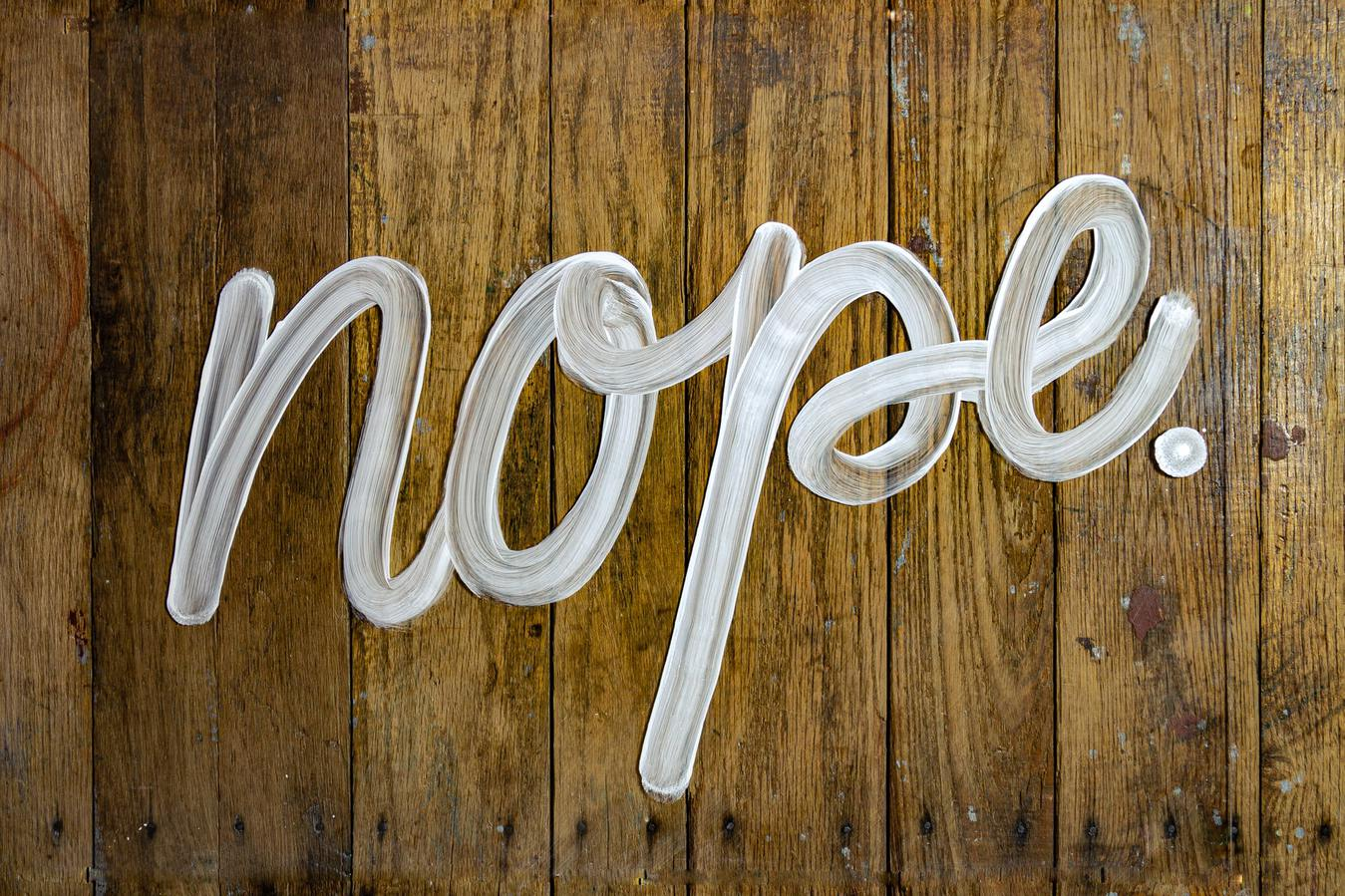 Nope spelled out against a wooden background